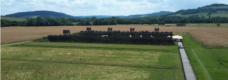 Au fond, le théâtre de la bataille avec, au premier plan, reconstitution des fortifications romaines - © Hubert Gouleret